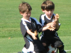 Brayson, left, and Dylan, right, compete in the traditional soccer ritual of fighting over a tree branch.